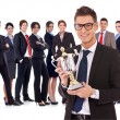 Businss man holding a trophy in fron of his team — Stock Photo