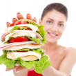 Young woman showing a sandwich — Stock Photo #12747115