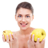 Young woman holding an apple and a pear — Stock Photo