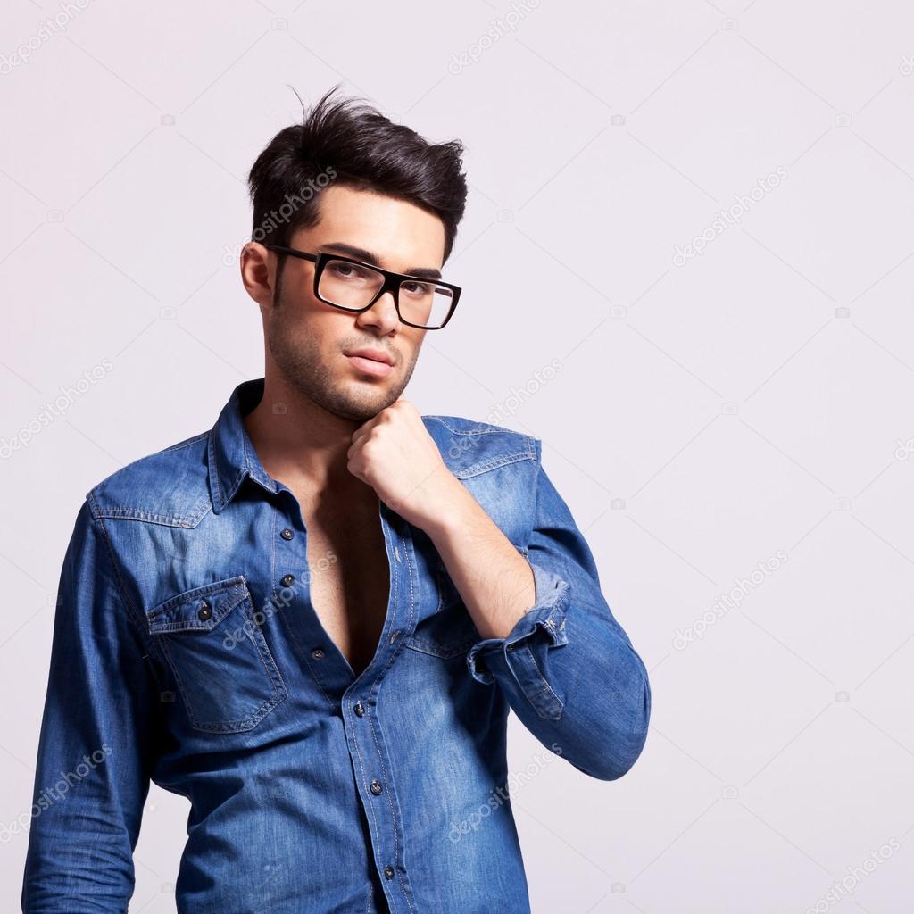 年轻时尚男模特举行他的衣领和寻找到相机上的灰色