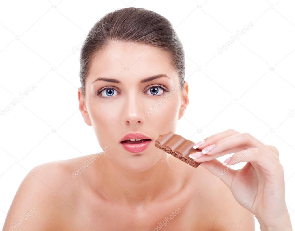 Close-up of a attractive young woman with a bitten chocolate in her hand. Young woman provoking chocolate cravings. On white background — Stock Photo #12747040
