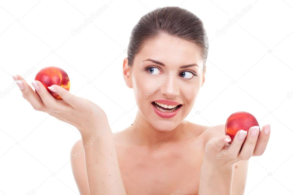 Picture of a gorgeous young woman holding two apples in her hand and watching at one of them. Young woman deciding which apple to choose. Over white background — Stock Photo #12747048