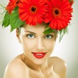 Gracefull young woman with red gerbera flowers in her hair — Stock Photo