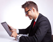 Young business man browsing on his tablet pad — Stock Photo