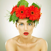 Amazed with red gerbera flowers on her head — Stock Photo