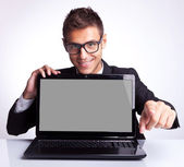 Man sitting at office desk with laptop pointing — Stock Photo