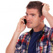 Confused young man on the phone — Stock Photo #13212248