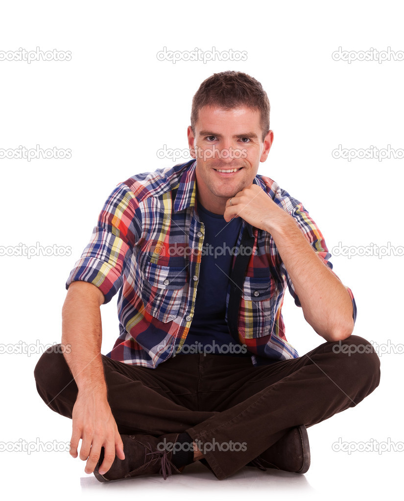 Young casual man sitting on the floor cross legged and smiling very charismatically to the camera. on white background — Stock Photo #13212273