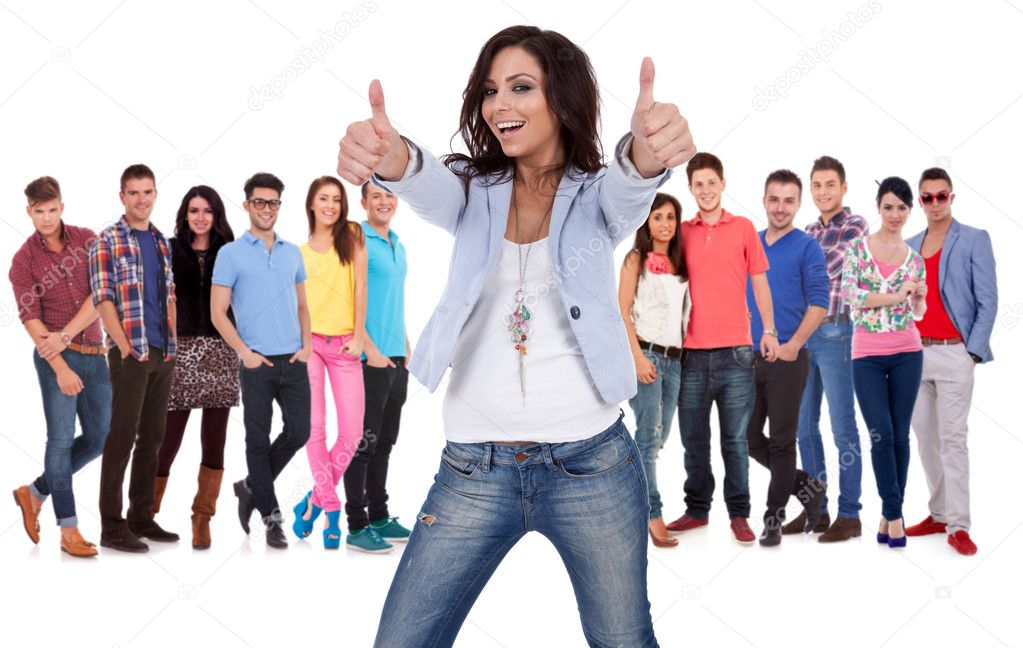 Casual young woman making the thumbs up ok sign in fron of a group of young smiling — Stock Photo #13212419