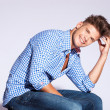 Fashion male model sitting and laughing — Stock Photo