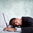 Business man sleeping on a laptop computer - Stock Photo