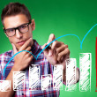 Casual man with glasses drawing a rising arrow - Stock Photo