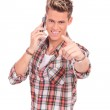 Young man on the phone pointing at you — Stock Photo #14286515