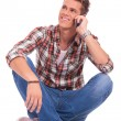 Foto Stock: Sitting and speaking on phone
