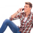Laying and speaking on the phone — Stockfoto