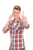 Casual man talking on the phone and showing victory sign — Stock Photo