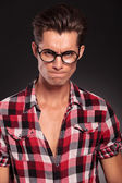 Angry casual young man wearing glasses — Stock Photo