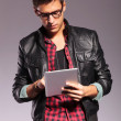 Young casual man with glasses working on tablet — Stock Photo