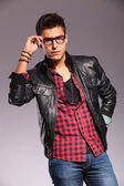 Man in leather jacket and jeans holding his glasses — Stock Photo