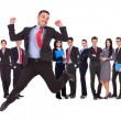 Business man jumping in front of his business team - Stock Photo