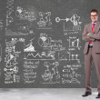 Business man in front of a wall with big plans - Stock Photo