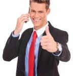 hombre de negocios demostrando los pulgares para arriba en teléfono — Foto de Stock