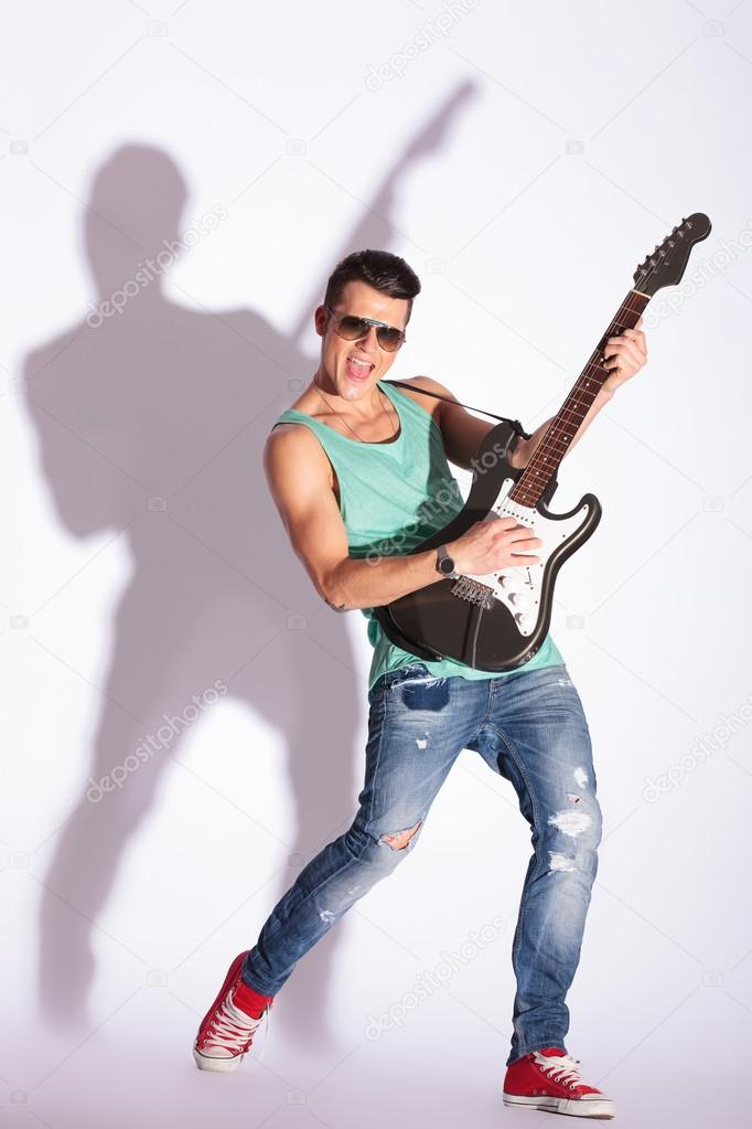 Young guitarist model playing on electric guitar and shouting, while looking at the camera, on a gray background with hard shadow — Stock Photo #19117381