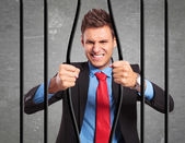 Businessman bending the bars of his prison — Stockfoto