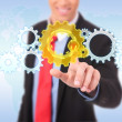 Business man pushing a cog button - Stock Photo