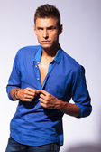 Sexy man unbuttoning blue shirt — Stock Photo