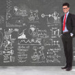 Business man stands in front of blackboard - Stock Photo