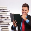 Man at desk reading book - Foto Stock