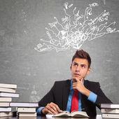 Hombre leyendo un libro y pensando en un montón de cosas — Foto de Stock
