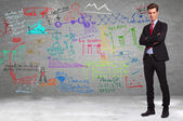 Business standing in front of a wall full of calculations — Stock Photo