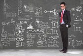 Business man stands in front of blackboard — Stock Photo