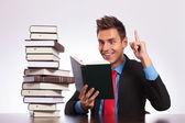 Reading man has an idea at desk — Stock Photo