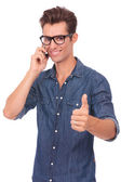 Man on the phone shows thumb up — Stock Photo