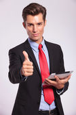 Holding tablet & making thumbs up gesture — Stockfoto