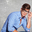 Fashion young man holding his glasses — Stock Photo