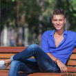 Man posing on bench in park - Foto Stock
