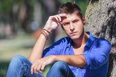 Pensive man sitting next to tree — Stock Photo