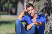 Serious man sits at a tree in park — Stock Photo