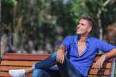 Man on bench looks away — Stock Photo