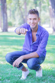 Crouched man pointing at you in park — Stock Photo