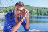 Man posing at table near lake — Stock Photo