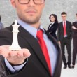 Leader of a businessteam holding the white king of chess — Stockfoto