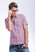 Casual man adjusting specs — Stockfoto