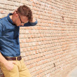 Casual man standing upset by brick wall — Stock Photo