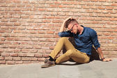 Casual man sits upset by wall — Stock Photo