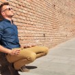 Casual man sits by wall — Stock Photo #25736145